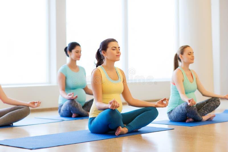 Glückliche schwangere Frauen, die Yoga in der Turnhalle ausüben lizenzfreie stockfotos