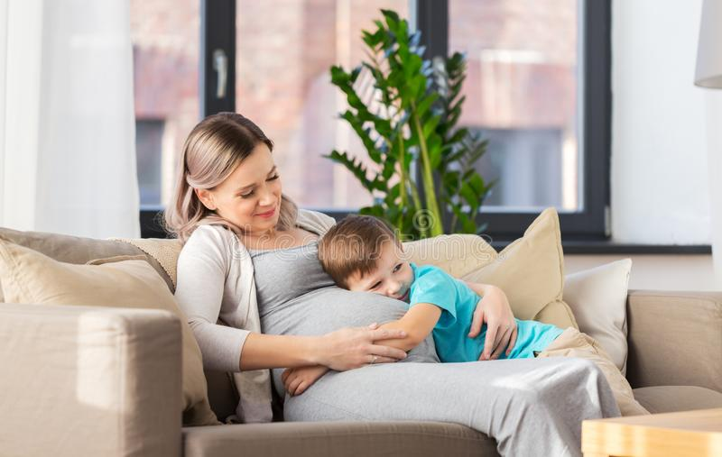 Glückliche schwangere Mutter und Sohn, die zu Hause umarmt stockbild