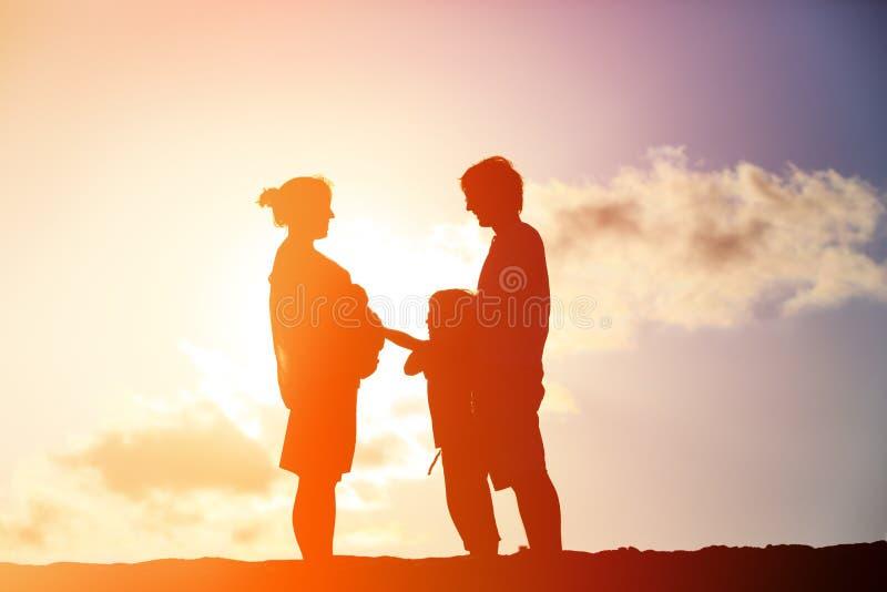 Glückliche schwangere Mutter und Vater mit Sohn bei Sonnenuntergang stockbild