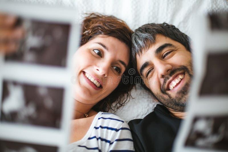 Glückliche schwangere Paare auf dem Bett, welches die Ultraschallbilder ihres Babys betrachtet lizenzfreie stockbilder