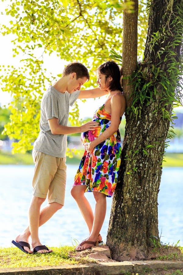 Glückliche schwangere Paare, die am ttopical Park im Rücklicht stehen stockbild