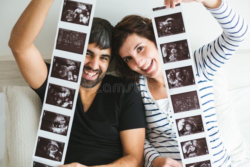 Glückliche schwangere Paare, die Ultraschallbilder ihres Babys zeigen lizenzfreie stockbilder