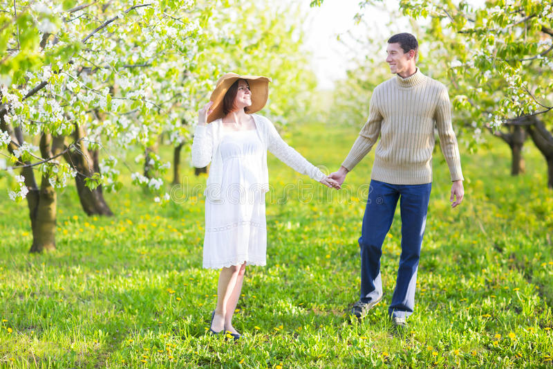 Glückliche schwangere Paare im Blütengarten lizenzfreies stockfoto