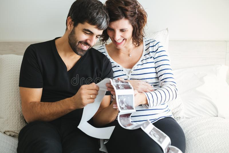 Glückliche schwangere Paare, welche die Ultraschallbilder ihres Babys betrachten lizenzfreies stockfoto