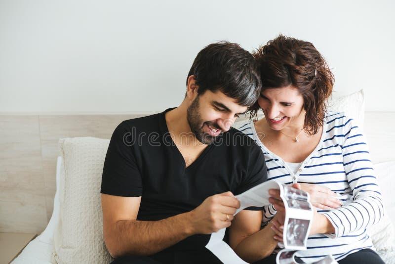 Glückliche schwangere Paare, welche die Ultraschallbilder ihres Babys betrachten lizenzfreie stockbilder