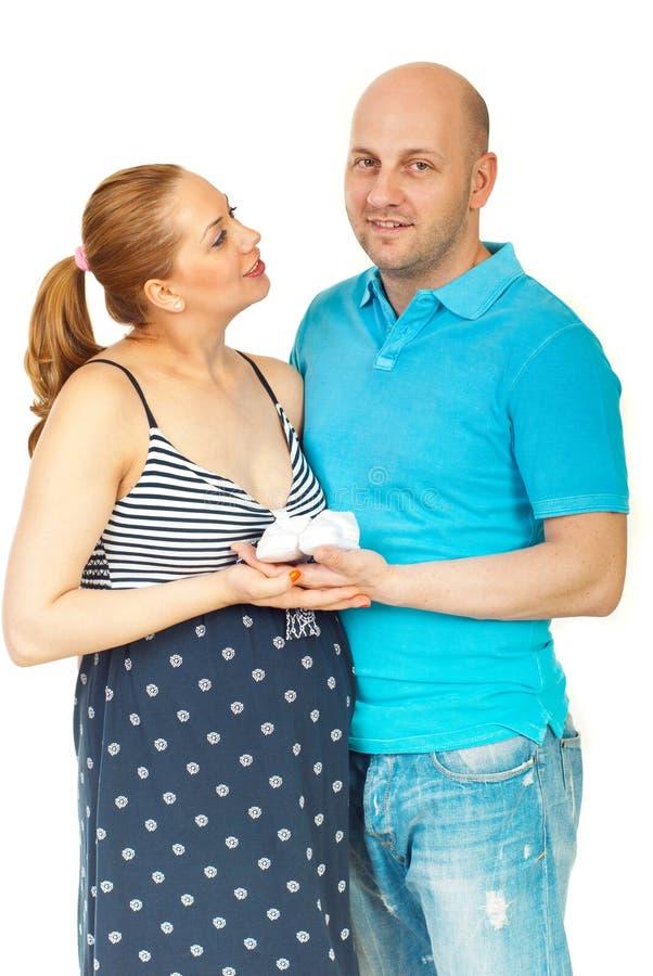 Glückliche schwangere Paarholding-Babyschuhe stockbild