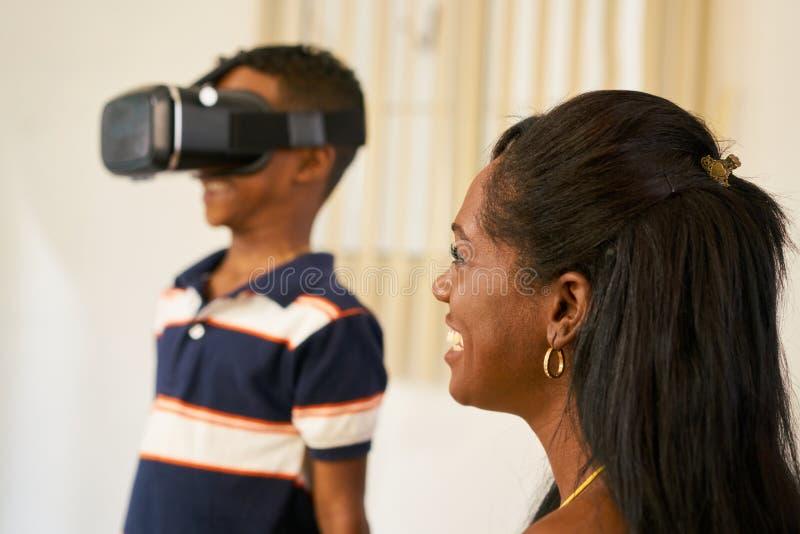 Glückliche schwarze Familie, die mit Köpfen der virtuellen Realität der Schutzbrillen-VR spielt stockfotos