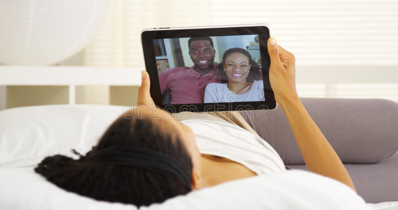 Glückliche schwarze Frau, die mit Freunden auf Tablette plaudert lizenzfreies stockbild