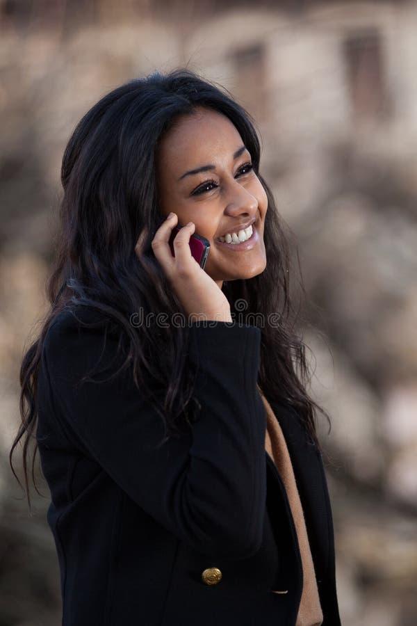 Glückliche schwarze Jugendliche, die einen Handy verwendet lizenzfreie stockfotografie