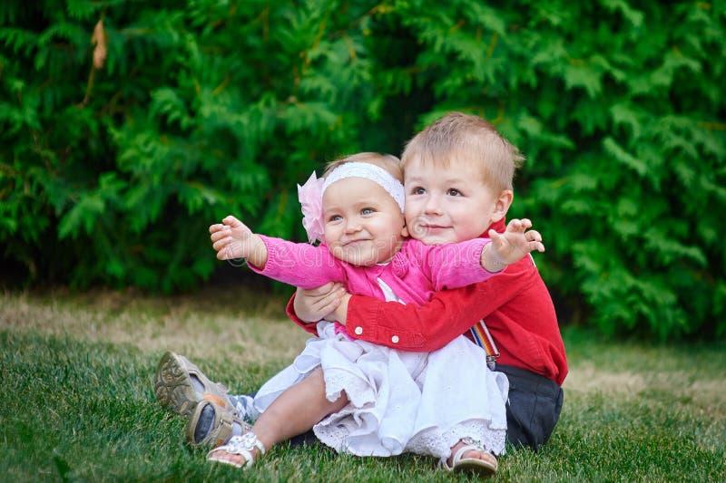 Glückliche Schwester und Bruder zusammen im Parkumarmen lizenzfreies stockfoto