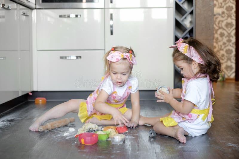 Glückliche Schwesterkindermädchen backen Plätzchen, kneten Teig, spielen mit Mehl und Lachen in der Küche stockfotos