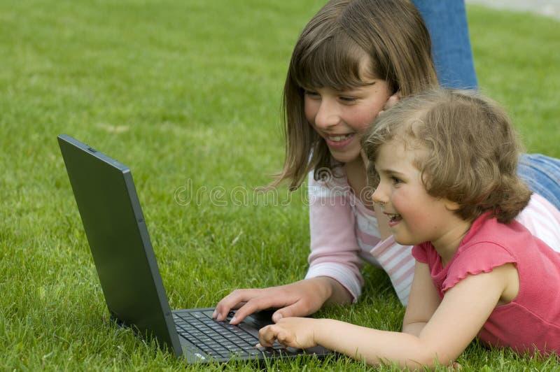Glückliche Schwestern mit Computer stockfoto