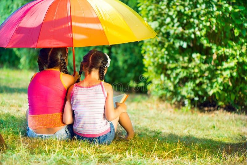 Glückliche Schwestern unter buntem Regenschirm im Park lizenzfreie stockfotos