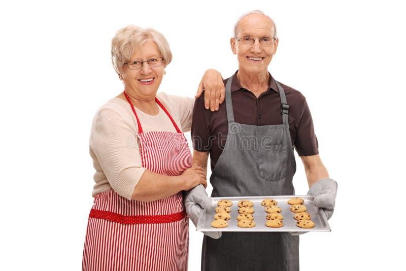 Glückliche Senioren mit einem Behälter von frisch gebackenen Plätzchen stockfotografie