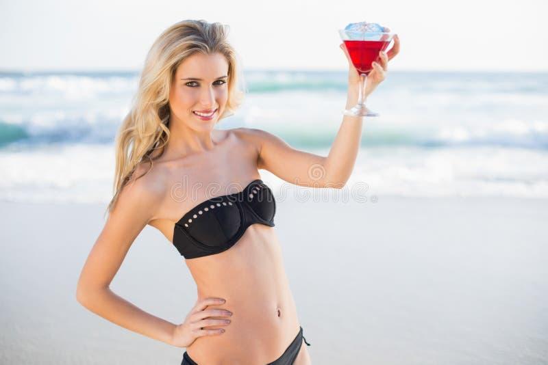 Glückliche sexy Blondine im eleganten Bikini, der Cocktail hält stockfoto