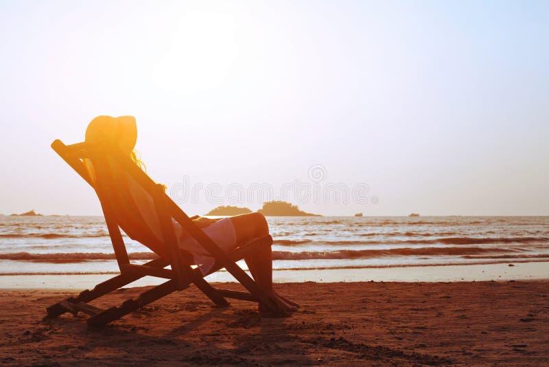 Glückliche Sommerstrandurlaube, Frau, die im deckchair, tropische Ferien sich entspannt stockfotos