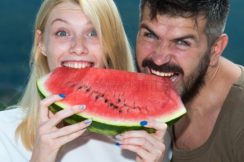 Glückliche sorglose Paare essen Wassermelone Vitamine und gesundes Konzept Genießen einer Wassermelone Paarfreunde, die a essen lizenzfreie stockfotos