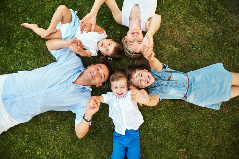 Gl?ckliche spielerische Familie, die drau?en auf Gras liegt Eltern mit Kindern im Sommer Mutter, Vati und Kinder lizenzfreie stockbilder