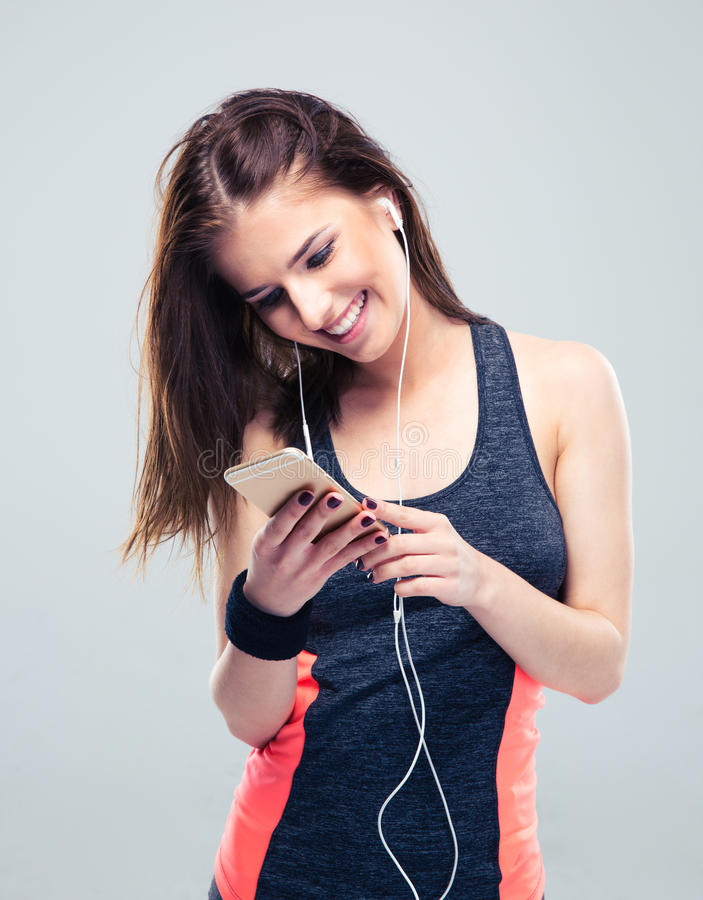 Glückliche Sportfrau, die Smartphone verwendet lizenzfreie stockfotos
