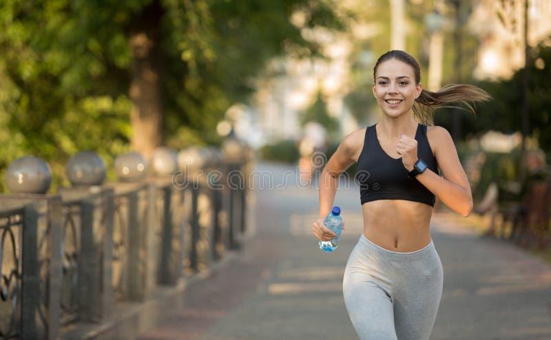 Glückliche sportliche tausendjährige Frau, die auf Kai läuft stockfotos