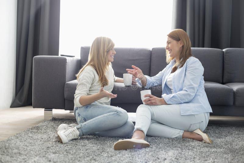 Glückliche sprechende Mutter und Tochter beim Trinken des Kaffees im Wohnzimmer stockfoto