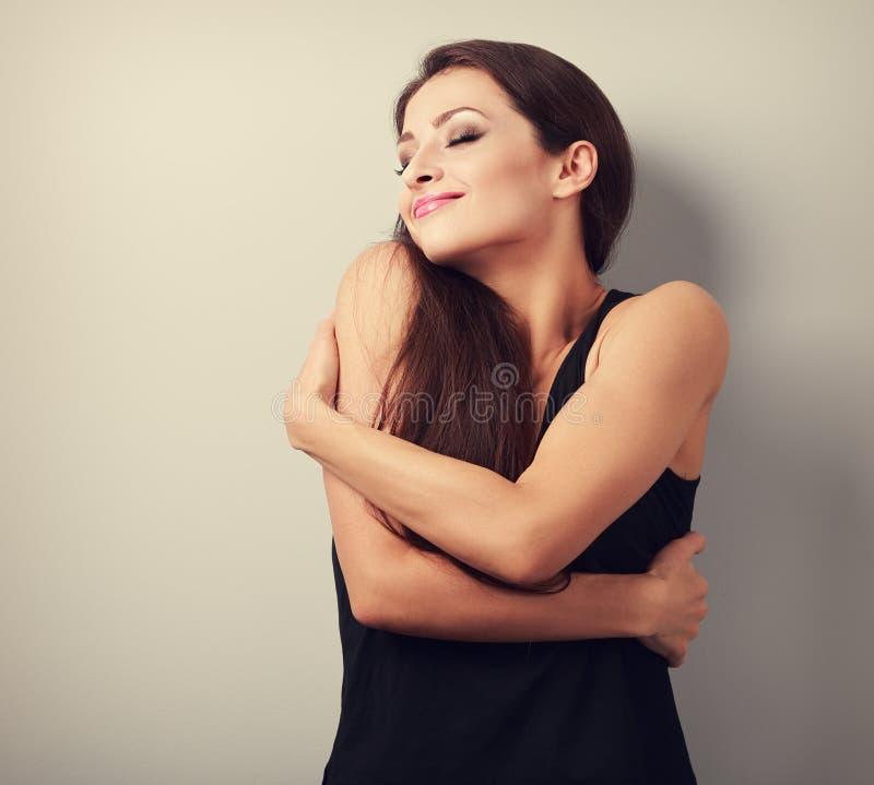 Glückliche starke sportliche Frau, die mit natürlichem emotionalem sich umarmt lizenzfreies stockfoto