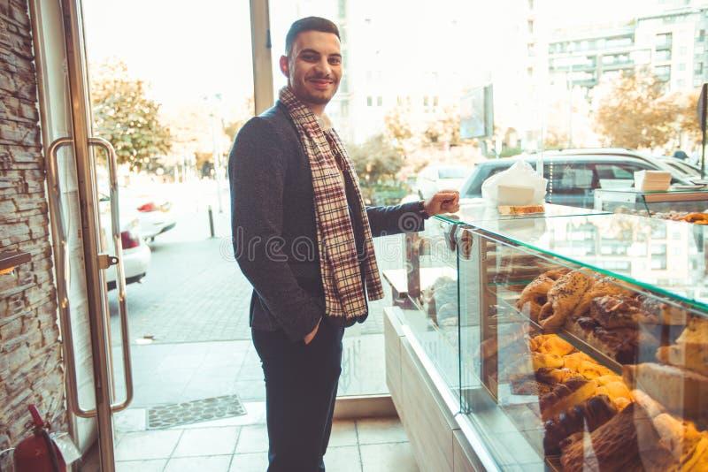 Glückliche Stellung des jungen Mannes in der Bäckerei lizenzfreie stockbilder