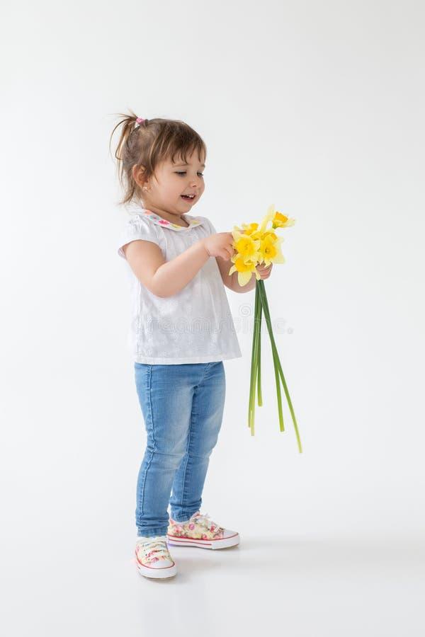 Glückliche Stellung des kleinen Mädchens lokalisiert über dem weißen Hintergrund, der Blumen hält lizenzfreies stockfoto