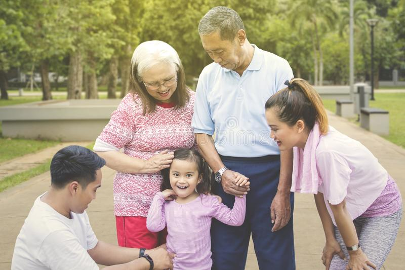 Glückliche Stellung des kleinen Mädchens mit ihrer Familie im Park lizenzfreies stockfoto