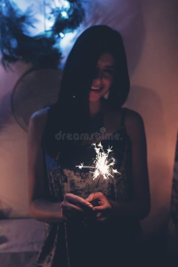 Glückliche stilvolle Frau, die ein brennendes Wunderkerzefeuerwerk Bengal L hält lizenzfreies stockbild