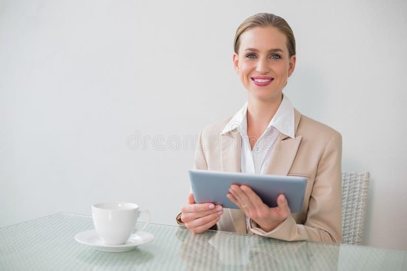 Glückliche stilvolle Geschäftsfrau, die Tablette verwendet lizenzfreie stockfotos