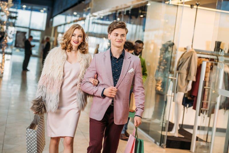 glückliche stilvolle junge Paare mit den Einkaufstaschen, die zusammen gehen lizenzfreies stockbild