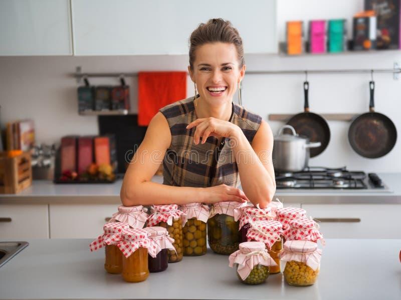 Glückliche, stolze Frau in der Küche mit Gläsern haus-konservierten Früchten stockfotografie