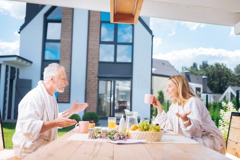 Glückliche strahlende Paare, die emotionales Gespräch beim Essen ihres Frühstücks haben stockfotos