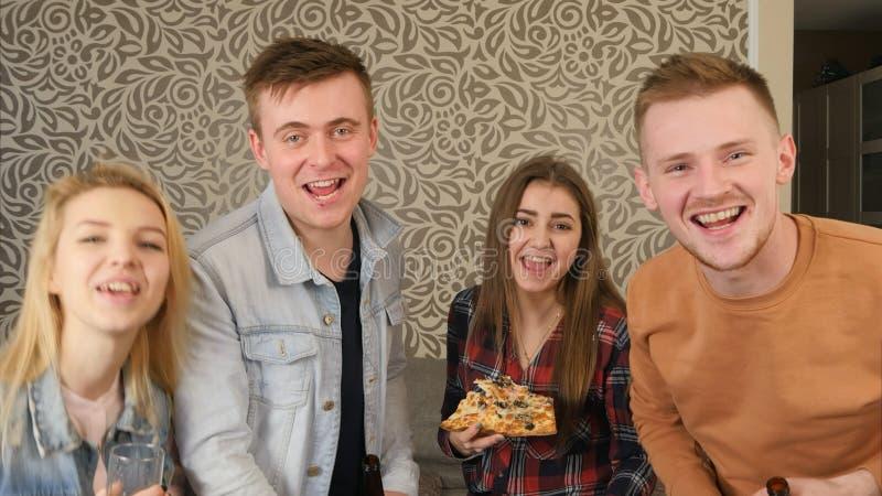 Glückliche Studenten beglückwünschen ihren Freund mit Geburtstag zu einer Kamera stockfotografie
