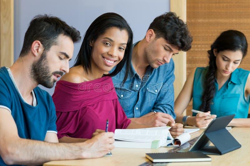 Glückliche Studenten an der Bibliothek lizenzfreie stockfotos