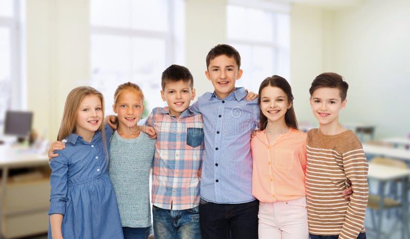 Glückliche Studenten, die in der Schule umarmen lizenzfreie stockbilder