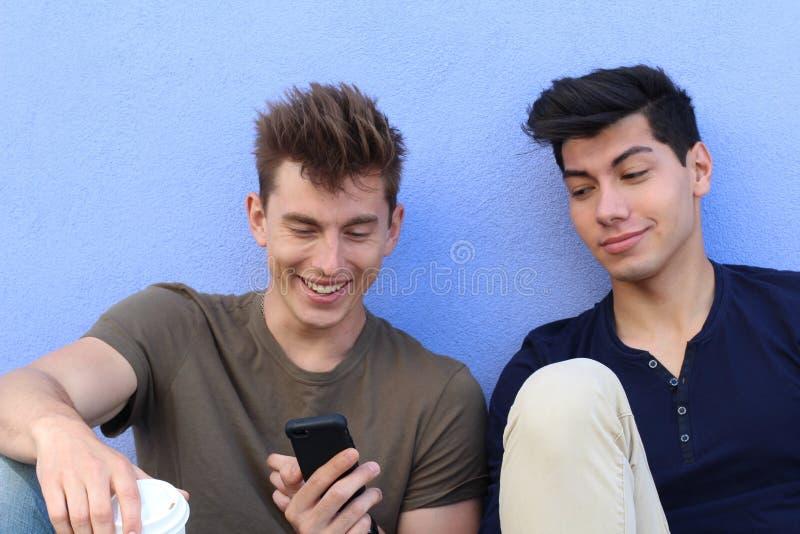 Glückliche Studenten, die draußen Smartphone auf dem Campus an der Universität betrachten lizenzfreie stockfotografie