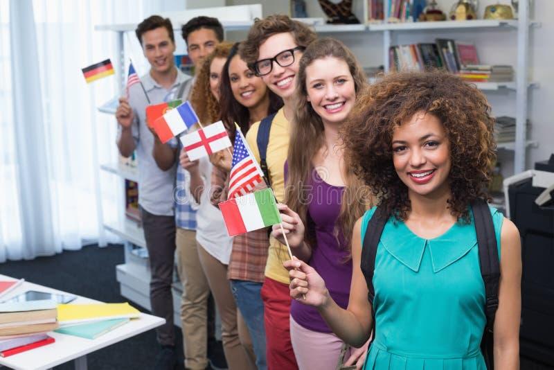 Glückliche Studenten, die internationale Flaggen wellenartig bewegen lizenzfreie stockbilder