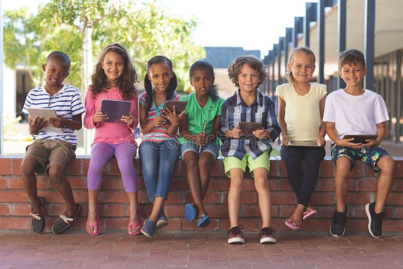 Glückliche Studenten, die mit digitaler Tablette auf Backsteinmauer am Korridor sitzen lizenzfreie stockbilder