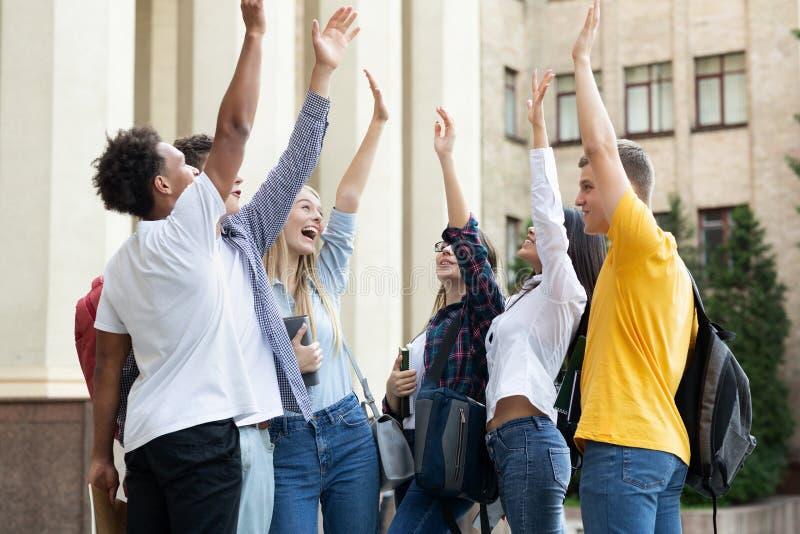 Glückliche Studenten, die nahe Universität mit den angehobenen Händen stehen stockbild