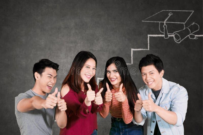 Glückliche Studenten zeigen Daumen oben im Klassenzimmer stockbild