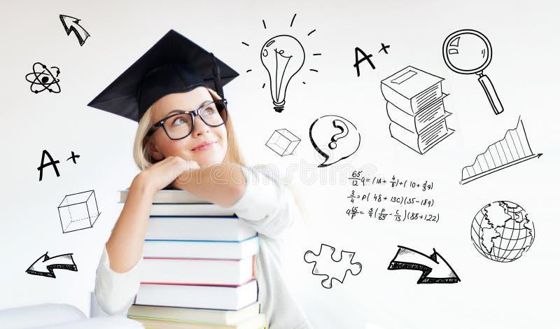 Glückliche Studentenfrau in der Doktorhut mit Büchern lizenzfreies stockfoto