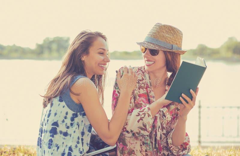 Glückliche Studentenfrauen der Freunde, die draußen Lesebuch studieren stockfotografie