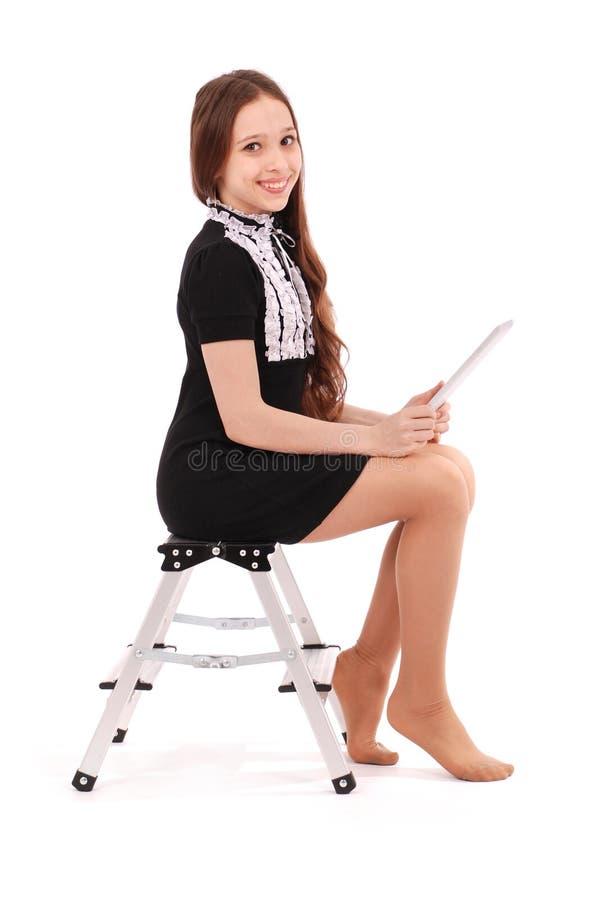 Glückliche Studentenjugendliche, die seitlich auf der Leiter mit t sitzt stockfoto