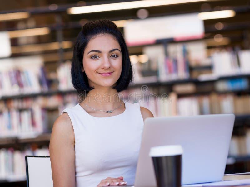 Glückliche Studentin an der Bibliothek stockfotos