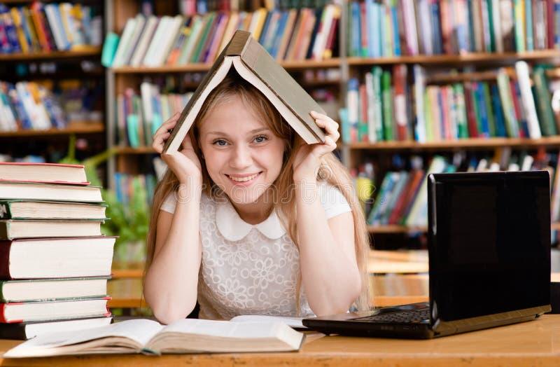 Glückliche Studentin in der Bibliothek stockfotografie