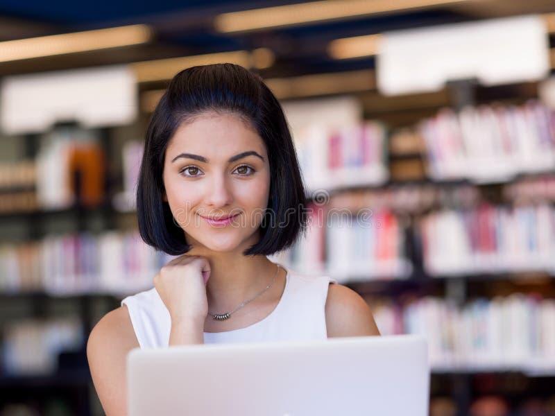 Glückliche Studentin an der Bibliothek stockfoto