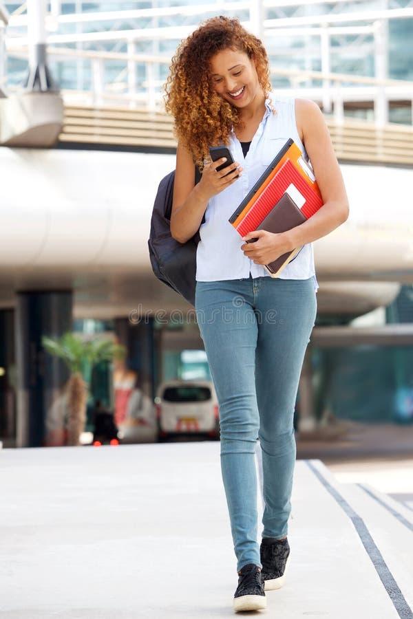 Glückliche Studentin des vollen Körpers, die draußen mit Mobiltelefon geht lizenzfreie stockfotos