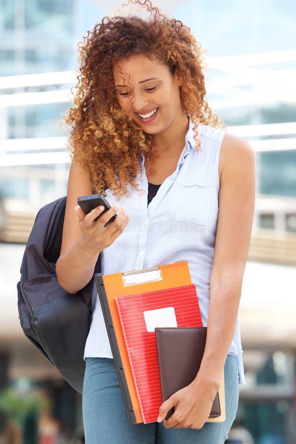 Glückliche Studentin, die auf dem Campus Handy betrachtet lizenzfreies stockbild